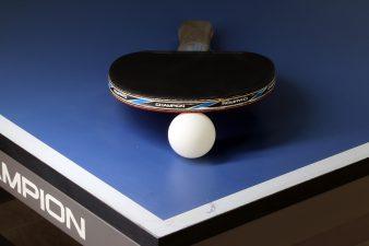 Racchetta nera e pallina bianca sul tavolo da ping pong professionale di colore blu