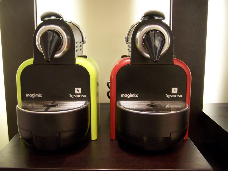 Macchine da caffè Nespresso posate su un tavolo, una colore verde lime e l'altra rossa.